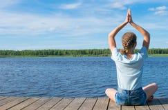Tegen de hemel, de meisjeszitting op de pijler, die yoga doen, in openlucht royalty-vrije stock afbeeldingen