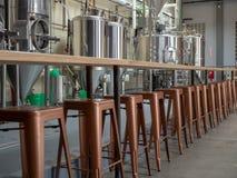 Tegenbovenkant en kuiperkrukken die voor brouwerijtanks zitten stock foto's