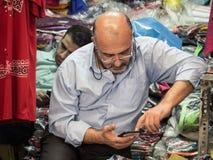 TEHERAN IRAN - AUGUSTI 14, 2016: Iranska köpmän som använder deras smartphones i den Teheran basaren Arkivfoto