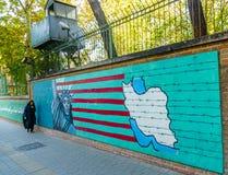 TEHERAN, IRAN - NOVEMBER 05, 2016: Iranian propaganda mural at the wall of former US embassy and veiled woman Royalty Free Stock Photos