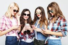 Tehnology, émotion et concept de personnes : quatre amis heureux de femmes partageant des médias sociaux dans un téléphone intell image stock
