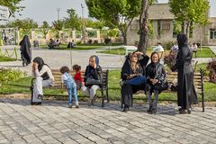 Women and children rest on bench in park, Tehran, Iran. Tehran, Iran - April 28, 2017: Girls in hijabs communicate by phone and with each other on a bench in a Royalty Free Stock Image
