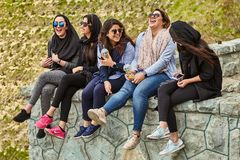 Iranian women chat and laugh,Tehran, Iran. Tehran, Iran - April 28, 2017: Iranian girls are sitting, chatting and laughing, some of them wear hijab stock photography