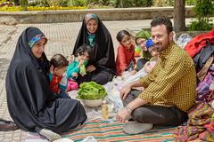 Big Iranian family on a picnic,Tehran, Iran. Tehran, Iran - April 28, 2017: Iranian man, children and women in hijabs sit in the park on a picnic on the day off Royalty Free Stock Images