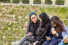 Iranian female students sitting and chatting,Tehran, Iran. Tehran, Iran - April 28, 2017: Iranian students sit in the park chatting and drinking cocktails Royalty Free Stock Photo