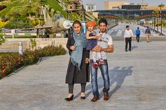 Iranian family walks in Holy Defense museum, Tehran, Iran. Tehran, Iran - April 28, 2017: Iranian woman in hijab and a man with a child in his arms walk in Holy Stock Photos