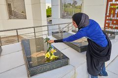 Gravestones in sacred defense garden-museum, Tehran, Iran. Tehran, Iran - April 28, 2017: Iranian woman in religious veil puts flower on tombstone of Military stock photography