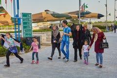 Visitors walk at the exhibition at Holy Defense,Tehran, Iran. Tehran, Iran - April 28, 2017: Iranian women in hijabs, man and children are walking around Holy royalty free stock photo