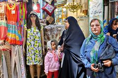 Muslim women stroll through the Tehran Grand Bazaar, Iran. Tehran, Iran - April 29, 2017: Muslim women, dressed in a religious veil, pass by a mannequin dressed Royalty Free Stock Image