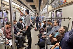 Muslims go by subway train, Tehran, Iran. Tehran, Iran - April 29, 2017: Muslims ride in the subway train, Iranian men stand and hold on to the railings Stock Image