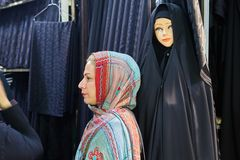 Woman in colored headscarf near the black cloth, Tehran, Iran. Tehran, Iran - April 29, 2017: One woman in a colored hijab, stands in the profile near the store Stock Photo