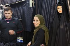 Smiling girl is selling black cloth, Tehran, Iran. Tehran, Iran - April 29, 2017: A smiling Muslim girl trades in a black cloth for a religious veil in the Stock Image