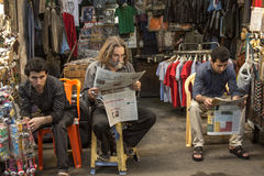 TEHRAN, IRAN - AUGUST 14, 2016: Iranian merchants reading newspapers in Farsi in Tehran main bazaar. Picture of young sellers from the main covered market of the Stock Photos