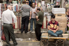 TEHRAN, IRAN - AUGUST 14, 2016: Merchants and delivery boys having a break and discussing in a covered street of Tehran bazaar Royalty Free Stock Photos