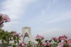 The Azadi Tower behind pink and white geranium cranesbill flower stock photography