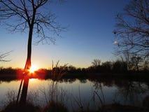 Teich oder See bei Sonnenaufgang oder Sonnenuntergang mit Blendenfleck Lizenzfreie Stockfotografie