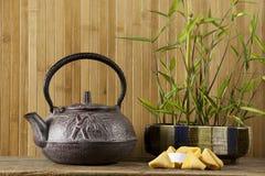Teiera, biscotti di fortuna e bambù rossi Fotografie Stock Libere da Diritti
