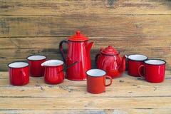 Teiera, brocca per latte e tazze di colore rosso Immagine Stock