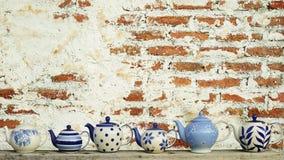 Teiera ceramica con il vecchio fondo d'annata del muro di mattoni Fotografia Stock