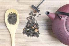 Teiera del ghisa con tè nero ed il cucchiaio di legno fotografia stock