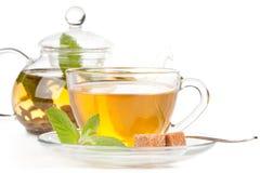Teiera e tazza di tè con la menta. immagini stock