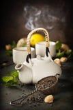 Teiera e tazze di tè con la menta ed il limone Immagini Stock