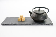 Teiera nera della ghisa e quattro cubi dello zucchero di canna accanto sui retti Fotografie Stock