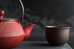 Teiera rossa del ferro sul fondo di colore scuro Fotografia Stock
