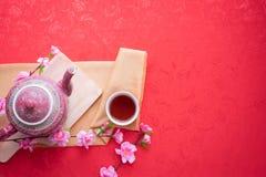 Teiera, tazza di tè e fiore di ciliegia sul fondo rosso della tovaglia, concetto del fondo cinese del nuovo anno Vista superiore fotografia stock