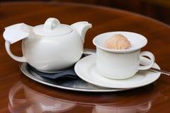 Teiera, tazza e biscotto Immagine Stock