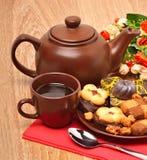 Teiera, tazza e sauser ceramici con i biscotti con i fiori immagini stock libere da diritti