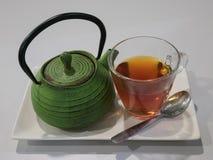 Teiera verde del ghisa con la tazza di tè su un piatto bianco con una s immagine stock