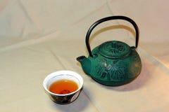 Teiera verde fatta del ghisa e di una ciotola di tè con le tovaglie di una tela della luce fotografia stock libera da diritti