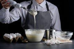 Teig, der aus dem Schneebesen ausl?uft manking Torte des Mannes Rezeptkonzept auf dunklem Hintergrund lizenzfreie stockbilder
