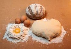 Teig in Form eines Herzens, eines runden Brotes, drei Eier und des Eigelbs umgeben durch Mehl Lizenzfreie Stockfotografie
