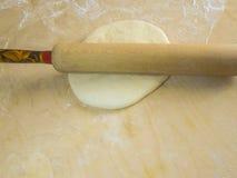 Teig und Mehl auf einem hölzernen Brett, einem Nudelholz und einem Tuch Stockfotos