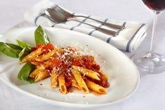 Teigwaren auf weißer Platte mit Tomatensauce. Lizenzfreies Stockfoto
