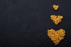 Teigwaren, die in Form vom Herzen auf schwarzem konkretem Hintergrund liegen Stockfotografie
