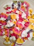 Teigwaren farfalle, italienisches Teigwarenmuster auf einer hölzernen Platte Verschiedene Farben von Fliege farfalle Teigwaren an stockbilder