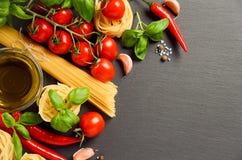 Teigwaren, Gemüse, Kräuter und Gewürze für italienisches Lebensmittel auf schwarzem Hintergrund Stockfotos