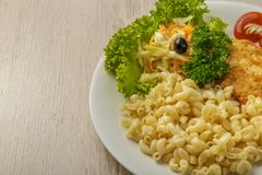 Teigwaren mit einem Stück gegrilltem Fleisch und Salat lizenzfreie stockfotos
