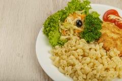 Teigwaren mit einem Stück gegrilltem Fleisch und Salat stockfotografie