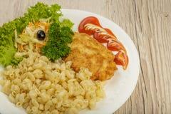 Teigwaren mit einem Stück gegrilltem Fleisch und Salat lizenzfreie stockbilder