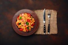 Teigwaren mit Käse, Kirschtomate, Gabel und Messer auf rostigem Hintergrund lizenzfreies stockbild