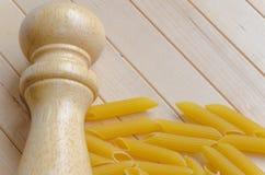 Teigwaren mit Salzgießmaschine auf hölzernem Hintergrund Stockbild