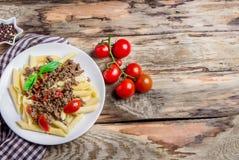 Teigwaren mit Tomaten und Fleisch auf hölzernem Hintergrund Lizenzfreie Stockbilder