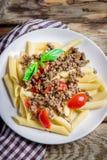 Teigwaren mit Tomaten und Fleisch auf hölzernem Hintergrund Stockfotografie