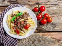 Teigwaren mit Tomaten und Fleisch auf hölzernem Hintergrund Stockfoto