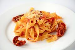 Teigwaren mit Tomatensauce, sonnengetrockneten Tomaten und Käse Stockbild
