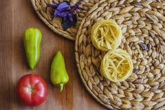 Teigwaren nisten, Tomate, Pfeffer, Basilikum auf einem Brett stockfotos